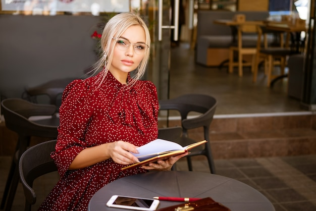 Jonge vrouw, een freelancer zit aan een tafel in een café op straat en schrijft in een notitieblok