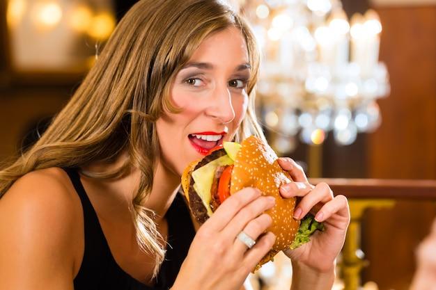 Jonge vrouw, een gastronomisch restaurant, eet een hamburger, ze gedraagt zich ongepast