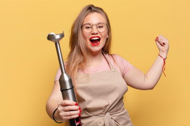 Jonge vrouw. een triomf vieren als een winnaar bakker blender concept