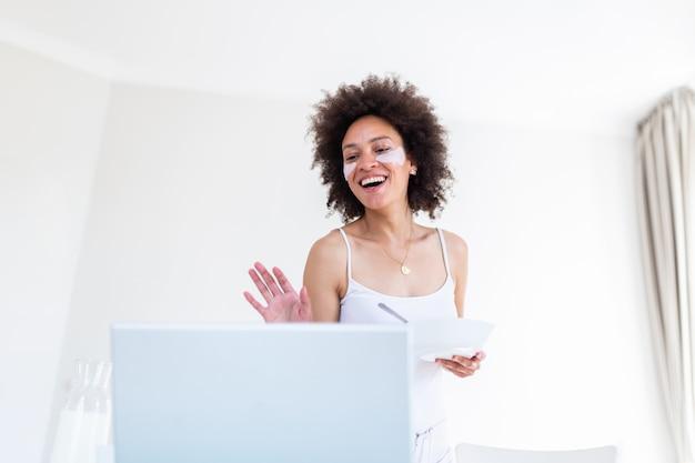 Jonge vrouw eet graag cornflakes als ontbijt terwijl ze naar een laptopcomputer kijkt en via een videogesprek met haar vrienden praat.