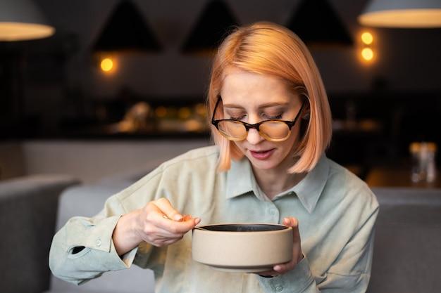 Jonge vrouw eet soep in een café en houdt een bord in haar handen