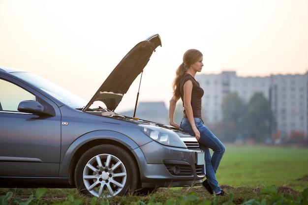 Jonge vrouw en een auto met geknapte kap. transport, voertuigen problemen en storingen concept.