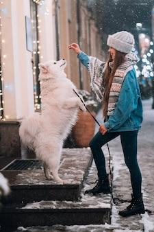 Jonge vrouw en een witte hond die trucs op een straat toont