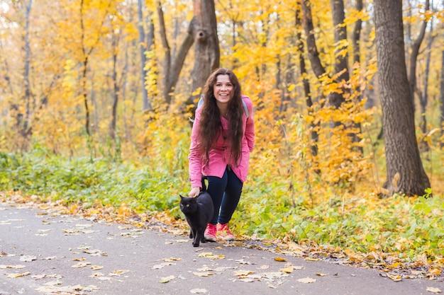 Jonge vrouw en een zwarte kat in het de herfstpark