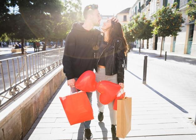Jonge vrouw en glimlachende man met pakketten en ballonnen plezier op straat