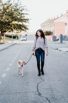 Jonge vrouw en haar hond buiten lopen door de straat