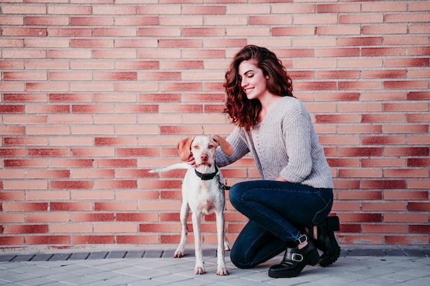 Jonge vrouw en haar hond in de stad. staande bij een bakstenen muur