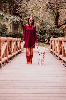 Jonge vrouw en haar jack russell hond wandelen in een park