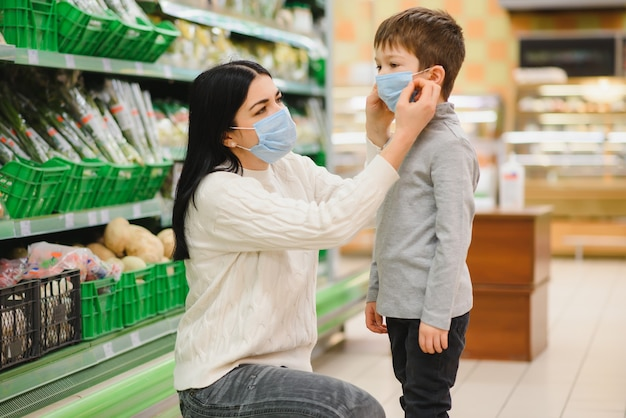 Jonge vrouw en haar kind met beschermende gezichtsmaskers kopen voedsel in een supermarkt tijdens de coronavirus-epidemie of griepuitbraak