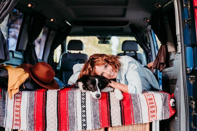 Jonge vrouw en haar leuke border collie-hond die in een bestelwagen ontspannen. reizen concept.