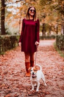 Jonge vrouw en haar leuke hond die van jack russell in een park lopen