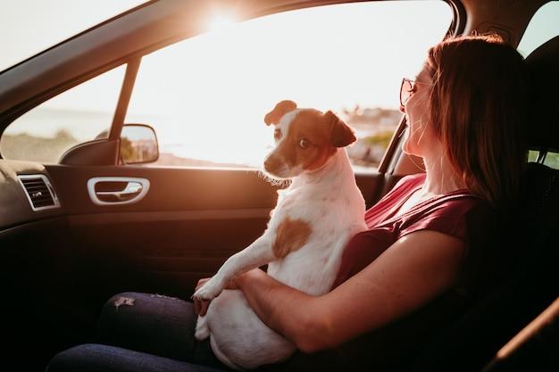 Jonge vrouw en haar leuke hond van jack russell in een auto bij zonsondergang. reis concept
