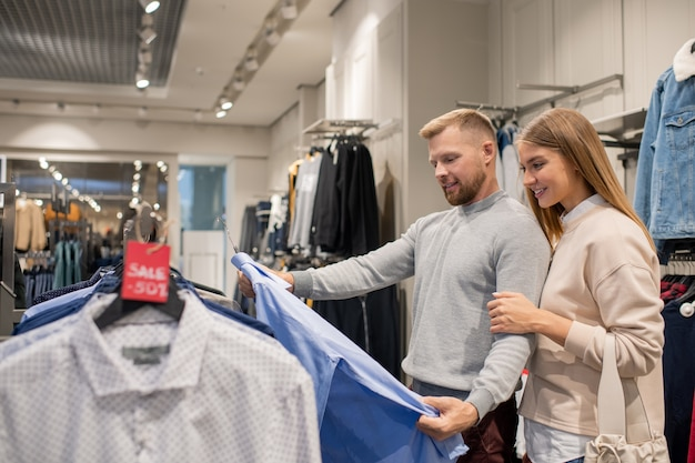 Jonge vrouw en haar man kijken naar blauw shirt terwijl staande door rek met kortingslabel en het kiezen van nieuwe kleren
