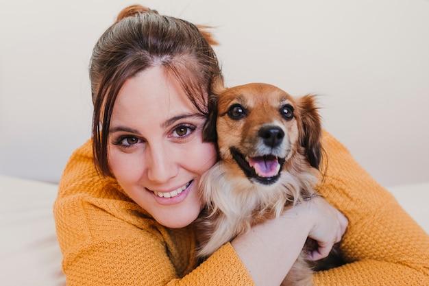 Jonge vrouw en haar schattige hond zittend op bed. liefde voor dieren concept. bovenaanzicht