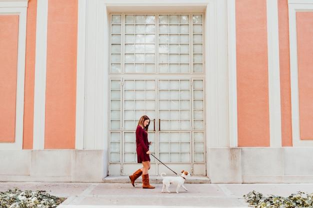 Jonge vrouw en haar schattige jack russell hond wandelen door de stad