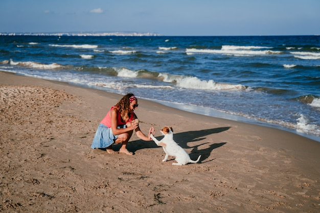 Jonge vrouw en haar schattige kleine jack russell terriër spelen op het strand