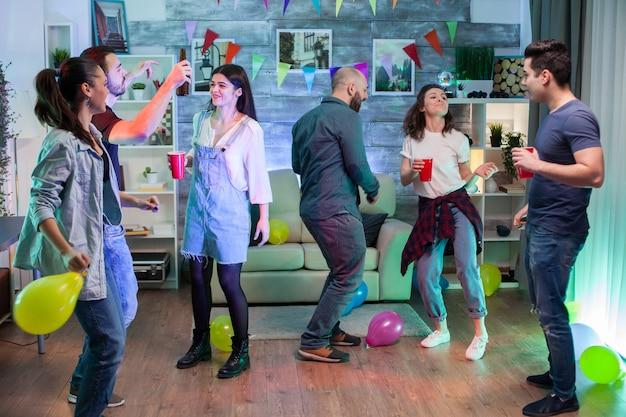 Jonge vrouw en haar vrienden op een feestje. mensen genieten van goede muziek.