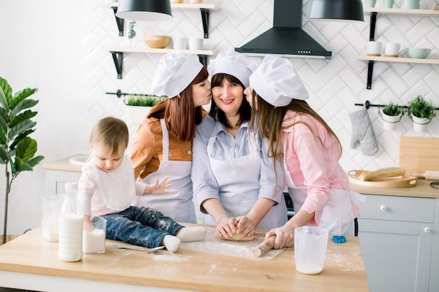 Jonge vrouw en haar zus, vrouw van middelbare leeftijd en kleine schattige dochter de voorbereiding van het deeg, bakken koekjes op moederdag. dochters kussen haar moeder