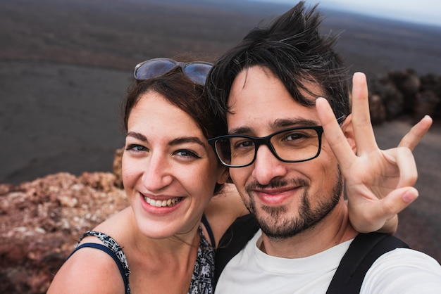 Jonge vrouw en jonge man op huwelijksreis omarmen direct lachend