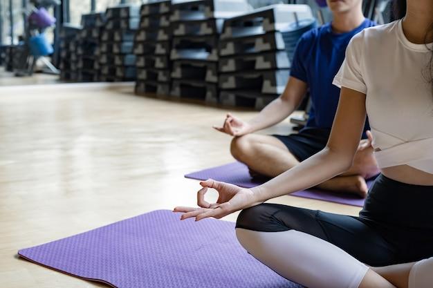 Jonge vrouw en jonge man zitten meditatie, yoga doen op de yoga mat in de fitnessruimte met kopieerruimte. jonge paren met oefening door samen binnen yoga te doen. concept van oefening met yoga.