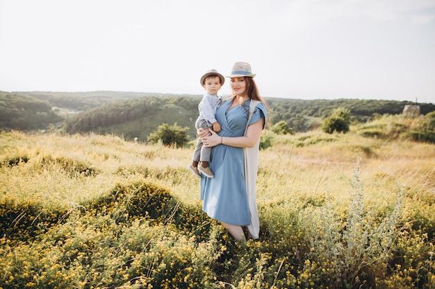 Jonge vrouw en kleine jongen in een veld, buitenshuis. moeder die haar zoon, glimlachend, zowel het dragen van vintage kleding en stro hoeden.
