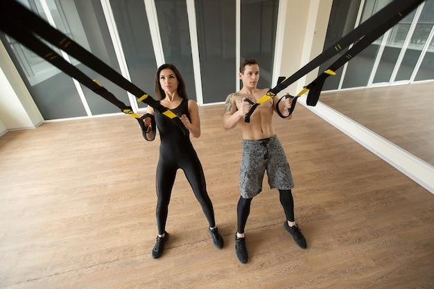 Jonge vrouw en man de opdrukoefeningen van de opleidingsoefening met trx geschiktheidsriemen in de gymnastiek