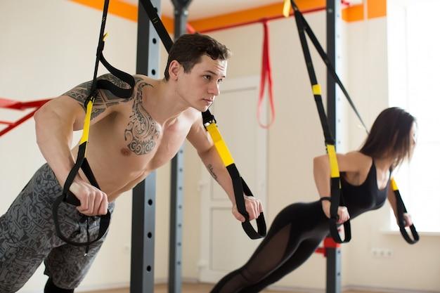 Jonge vrouw en man de opdrukoefeningen van de opleidingsoefening met trxfitness riemen in de de sporttraining gezonde levensstijl van het gymnastiekconcept.