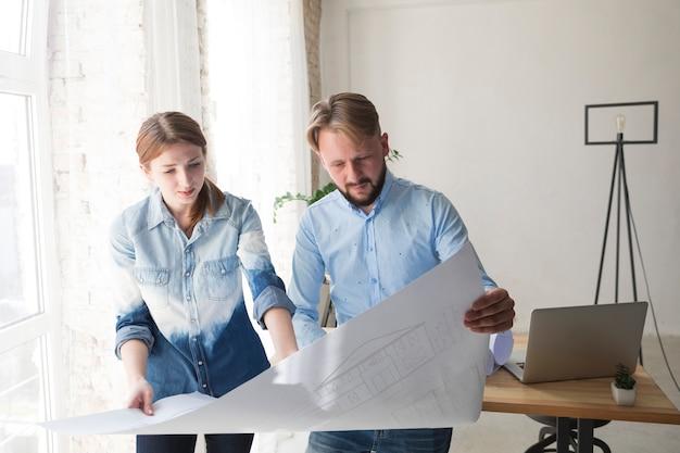 Jonge vrouw en man die aan blauwdruk op kantoor werken