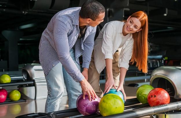 Jonge vrouw en man die kleurrijke kegelenballen nemen