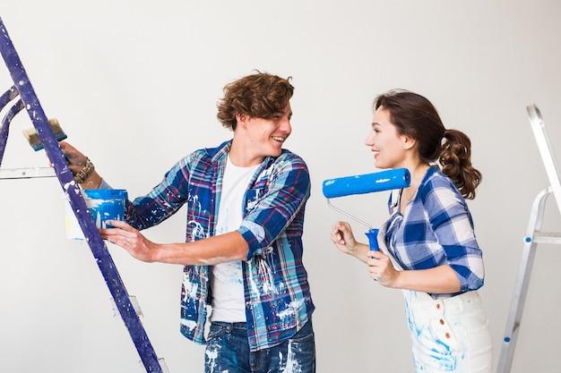 Jonge vrouw en man die reparatie met gelukkige gezichten doen.