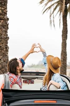 Jonge vrouw en man die symbool van hart tonen en uit auto leunen