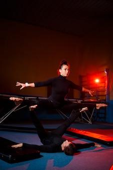 Jonge vrouw en man gymnasten doen acrobatische oefeningen in de sportschool. sportactiviteiten, gezonde levensstijl