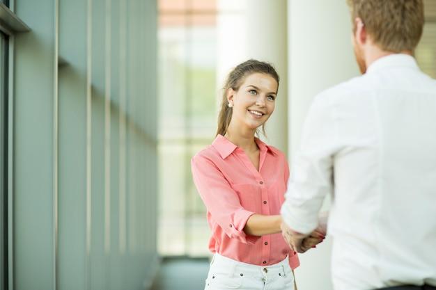 Jonge vrouw en man handshaking