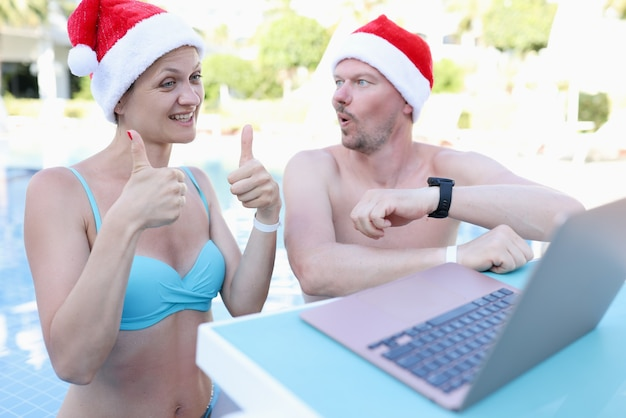Jonge vrouw en man in santa claus-hoeden in zwembad nodigen duimen omhoog gebaar uit en glimlachen in laptop