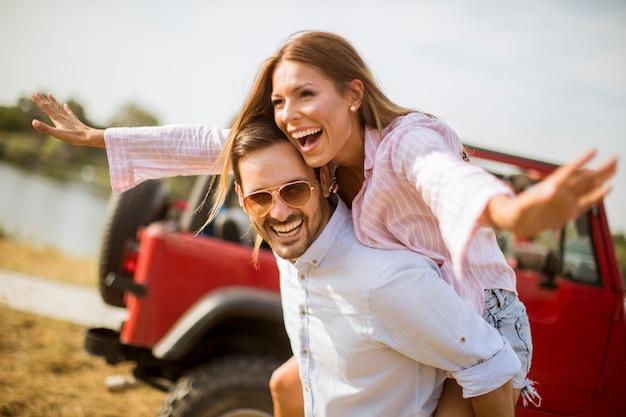 Jonge vrouw en man met plezier buiten in de buurt van de auto