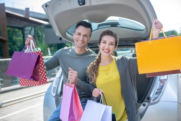 Jonge vrouw en man met veel aankopen in de buurt van de auto