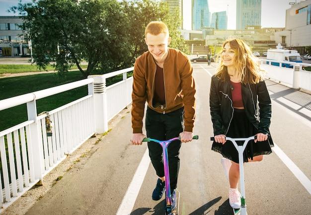 Jonge vrouw en man op kickscooter. meisje en jongen met rugzak rollen op elektrische scooter.