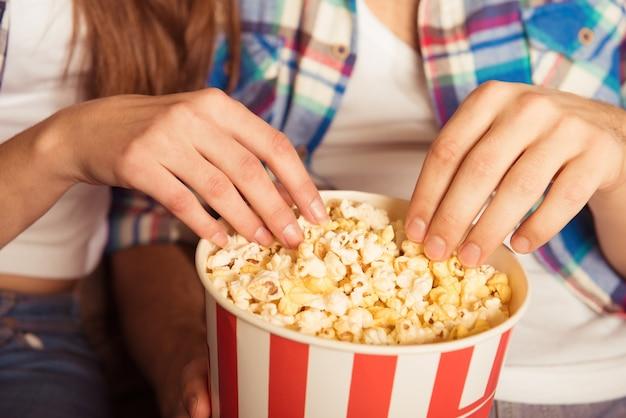 Jonge vrouw en man popcorn eten in de bioscoop