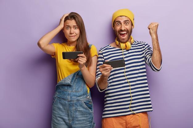 Jonge vrouw en man spelen videogames op smartphones, man toont vuist hobbel, verheugt zich over de overwinning, draagt gestreepte trui en koptelefoon, bezorgd vrouw staat in de buurt