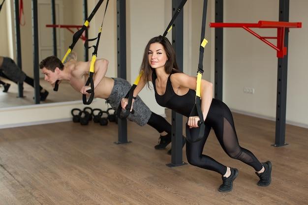 Jonge vrouw en man training oefenen push-ups met trx fitness riemen in de sportschool