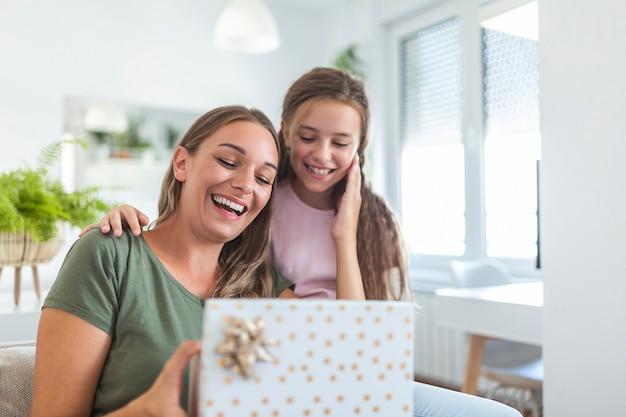 Jonge vrouw en meisje thuis vieren moederdag zittend op de bank dochter knuffelen moeder kussen wang moeder lachen vreugdevolle holding geschenkdoos