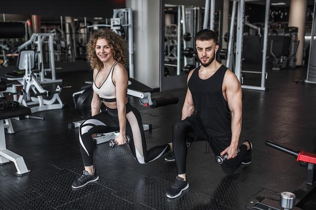 Jonge vrouw en personal trainer met dumbbell squats in gym