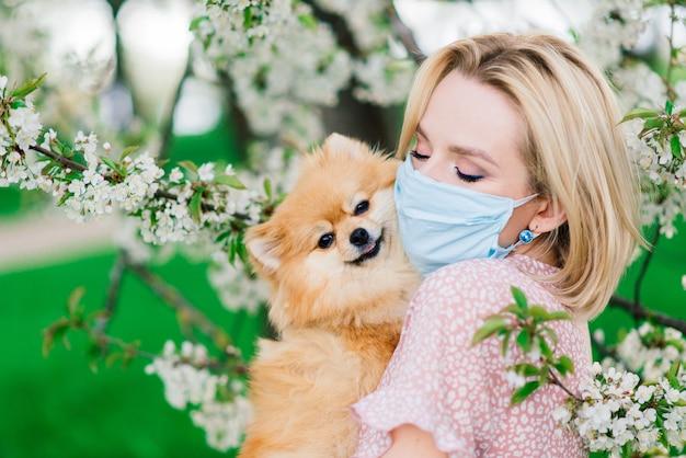Jonge vrouw en rode spitz met een medisch masker op haar gezicht op aard op een de lentedag. coronapandemie