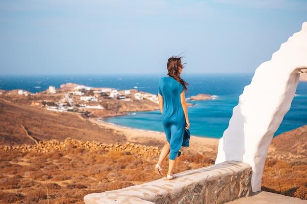 Jonge vrouw en traditionele witte kerk met uitzicht op zee in het eiland mykonos, griekenland