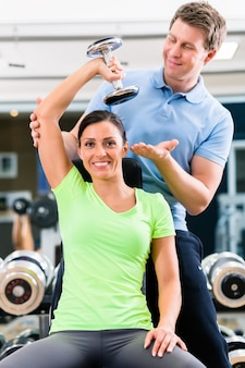 Jonge vrouw en trainer bij oefening in gymnastiek met gewichten van de halter