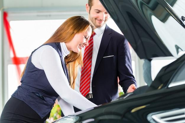 Jonge vrouw en verkoper met auto in het autohandel drijven