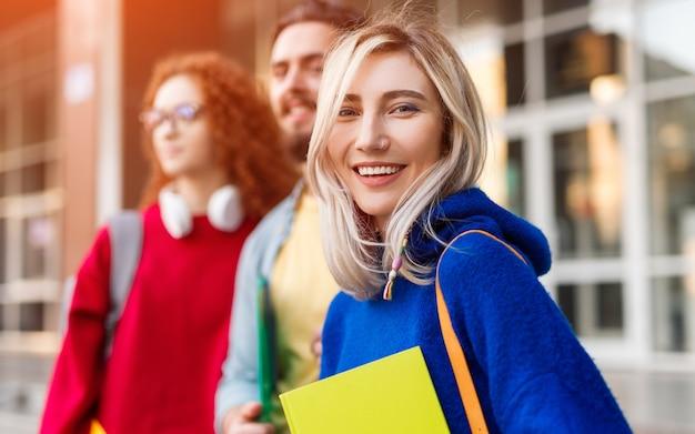 Jonge vrouw en vrienden met het glimlachen van het notitieboekje