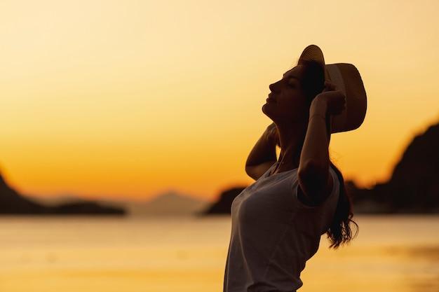 Jonge vrouw en zonsondergang op de oever van een meer