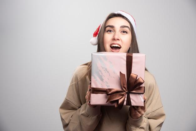 Jonge vrouw enthousiast over een doos met kerstcadeautjes.