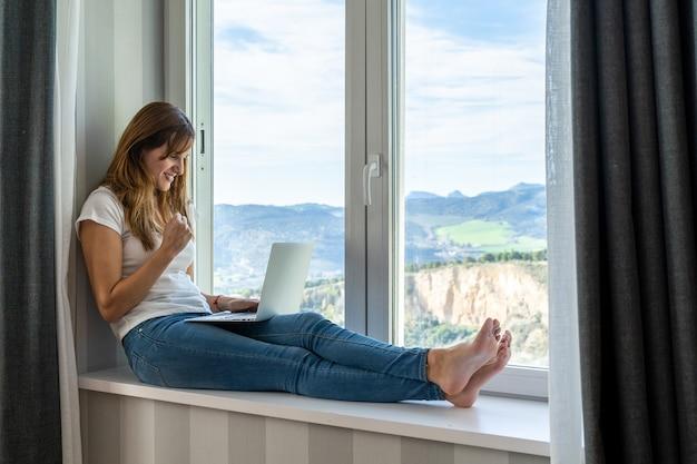 Jonge vrouw erg blij tijdens het gebruik van haar laptop. concept van werk of studie thuis.